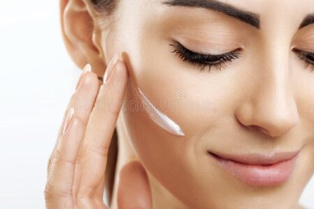 beauty-closeup-happy-young-woman-apply-cream-to-her-face-skincare-cosmetics-concept-skin-care-natural-applying-makeup-touching-145136435